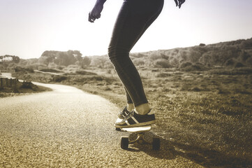 Low section of woman skateboarding on road against sky