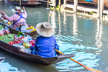 Traders are rowing boats to sell fruit at the floating market.Traditional floating market , Thailand.