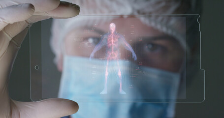 A futuristic physician, a surgeon, examines a technological digital holographic plate human body a medical mask, a cap brown eyes Concept futuristic medicine new technologies doctors laboratory future