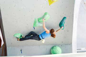 Woman making Free bouldering competition session at Indoor Rock Climbing wall