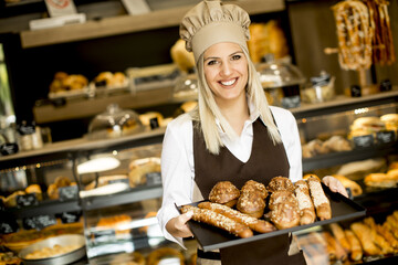 Beautiful female bakery posing with various types of pastries and breads in the baker shop