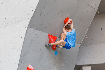 Sports Man professional climber on artificial climbing wall in bouldering gym