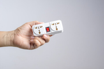 Hand holding universal traveler adapter plug with power switch