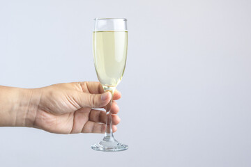 Hand holding glass of champagne for celebration on white backgroun