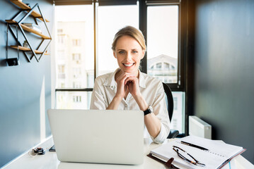 Positive attractive lady working in office cheerfully