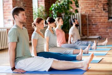 group of people doing yoga staff pose at studio