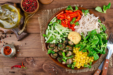 Healthy salad bowl with chicken, mushrooms, corn, cucumbers, sweet pepper and mix salad