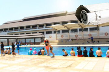 CCTV monitoring against blur of people at a swimming pool background.