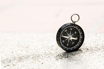 black compass on small gravel stone background, keep going concept
