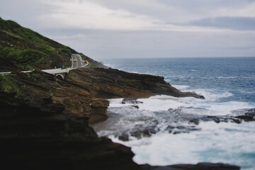 Tilt-shift image of road on mountain by sea against cloudy sky
