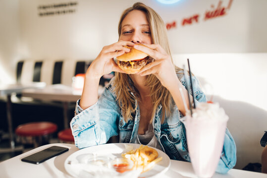 Young woman eating burger in restaurant
