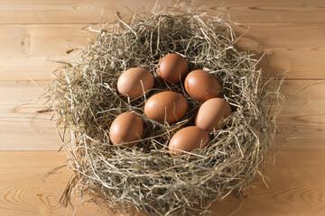 Brown chicken eggs in straw nest on wooden planks floor