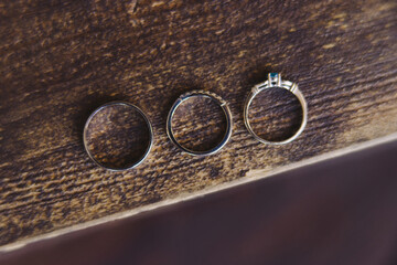 Wedding jewelery closeup. Wedding rings with diamonds and engagement ring with blue jemstone on wooden background. White gold, macro photography.