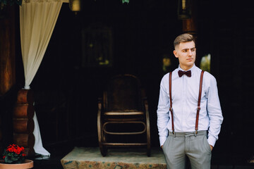 A handsome young man in a shirt, a bow tie, trousers and suspenders stands on the veranda of the house.