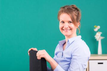 buisnessfrau sitzt lächelnd auf einem stuhl