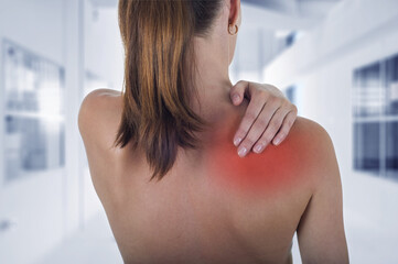 Woman with shoulder pain back, hospital background
