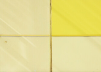 The wall of the house, trimmed with colorful panels, painted in bright colors. Yellow and beige