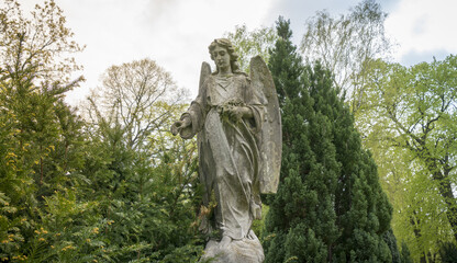 old sculpture of an angel in nature.