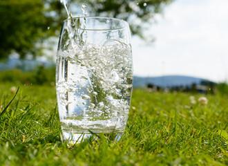 Einfallen von Wasser in das Glas im Sommer bei warmen Temperaturen