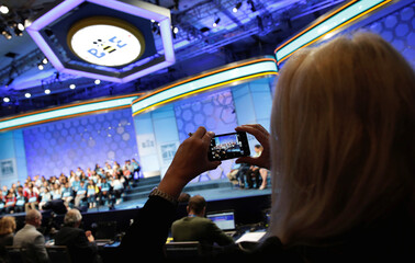 A woman takes a picture of the stage during the 2017 Scripps National Spelling Bee at National Harbor in Oxon Hill, Maryland