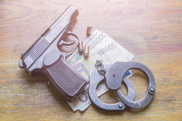 Gun, money and handcuffs on the wooden table. Crime concept