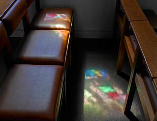 Durch farbiges Glasfenster gefiltertes Licht fällt auf eine Kirchenbank und auf den Boden