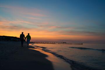 Ein Paar geht beim romantischen Sonnenuntergang am Strand spazieren