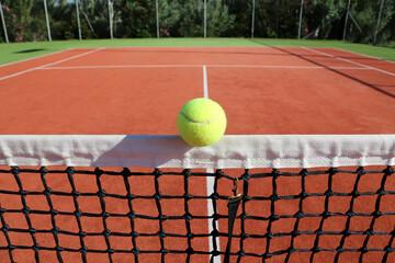 Gelber Tennisball triftt Netz auf rotem Tennisplatz, Symbolbild Tennis