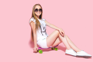 Cheerful young girl in sunglasses sitting on a skateboard on the pink background.