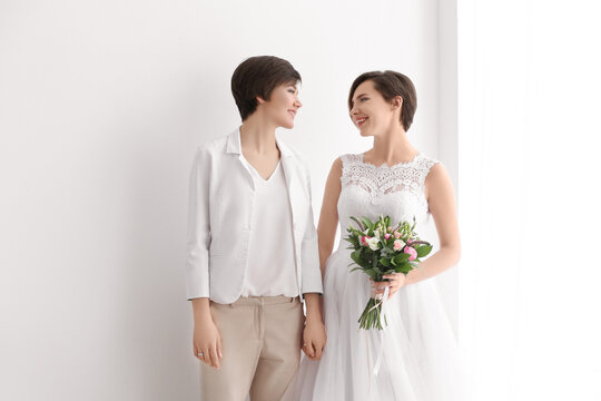 Gay wedding concept. Happy married lesbian couple on light background