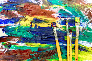 Artists oil paints multicolored abstract texture with brushes top view