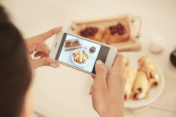 Woman photographing food with smart phone