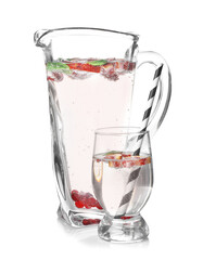 Jug and glass of refreshing lemonade on white background