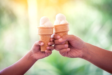 Mother and kid hands holding melting ice cream waffle cone together in green nature background