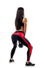 Young woman in sportswear makes deadlift with weight in in semi-squat position on white isolated background