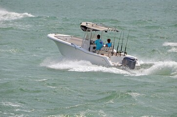 Couple in a small fishing boat making it's way through moderately choppy water on the florida intra-coastal waterway off Miami Beach.