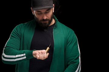 Sporty man with beard in a cap is holding golden e - cigarette mode. Studio shooting. Black background.