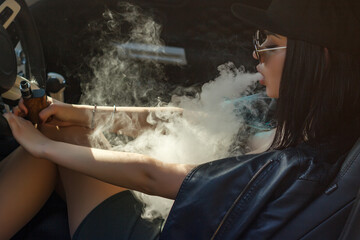 Young sexy woman is smoking (vaping) e-cigarette sitting in the car.