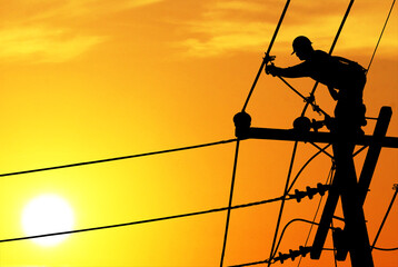 Shadow electricians repairing wire on electric power pole at the sunset blur Wall mural