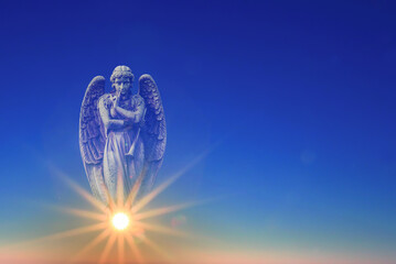 Angel over blue sky with rays of sun light with copy space
