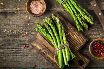 banches of fresh green asparagus on wooden background