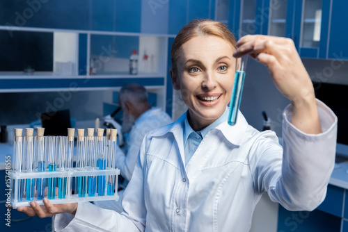 "happy chemist in lab coat holding tubes at laboratory"" Stock photo ..."