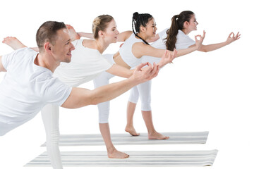 Side view of group of young women with trainer standing in Natarajasana yoga pose