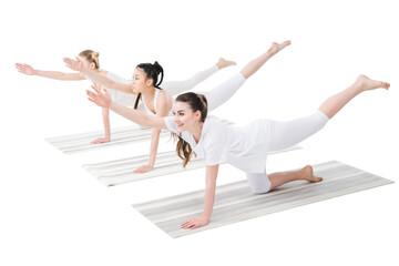 smiling women practicing bird dog pose on yoga mats isolated on white