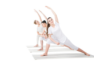 Smiling young women practicing Extended Side Angle Pose on yoga mats