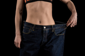 cropped shot of woman wearing large jeans isolated on black, weight loss concept