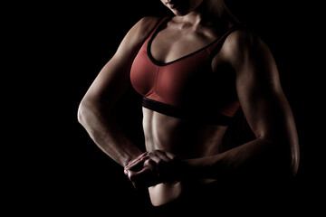 cropped view of sportswoman posing in sportswear and showing her muscular arms isolated on black
