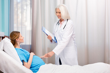 Smiling doctor with clipboard and stethoscope talking with pregnant woman lying in hospital bed