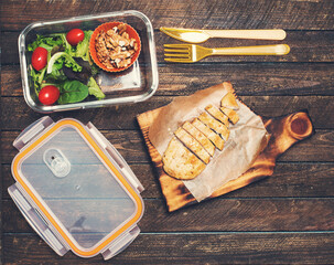 Preparing takeaway meal for children. School lunch box with salad, fried chicken and nuts on rustic wooden background. Healthy eating habits concept.