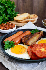 English breakfast: sausages, bacon, tomatoes, egg, beans in sauce, fried mushrooms, toast on a dark wooden background. Vertical view. Traditional classic food of England.